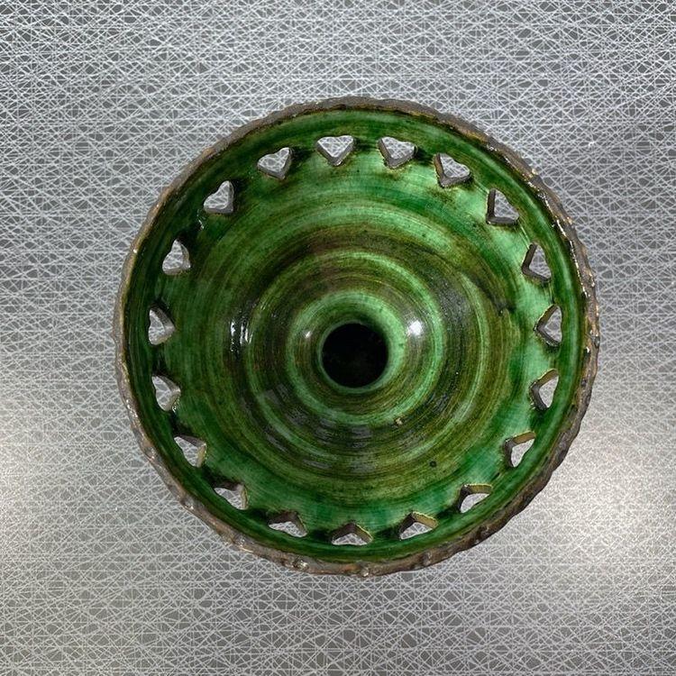 Ljusstake på fot i keramik med grön glasering och perforerad kant tagen ovanifrån