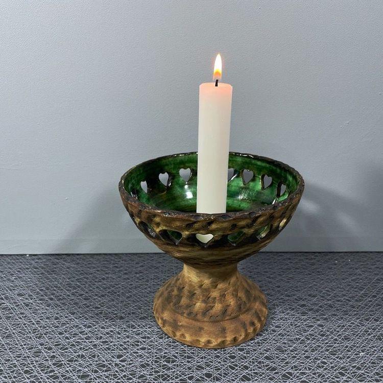 Ljusstake på fot i keramik med grön glasering och perforerad kant med vitt kronljus