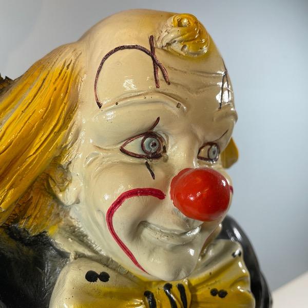 Bordslampa av Clown som håller i en lampa framifrån närbild clownansikte