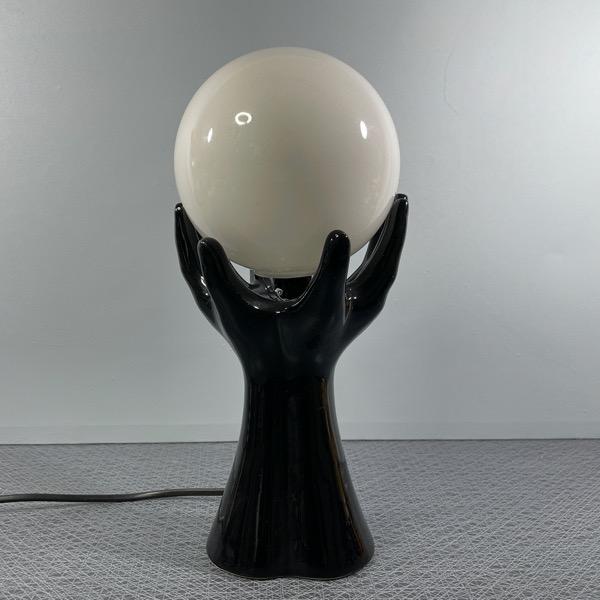 handlampa svart porslin händer som håller en en glaskula