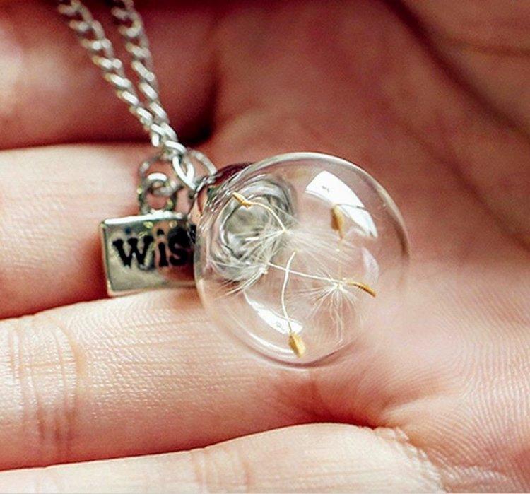 Halsband glaskupa med lösa maskrosfrön