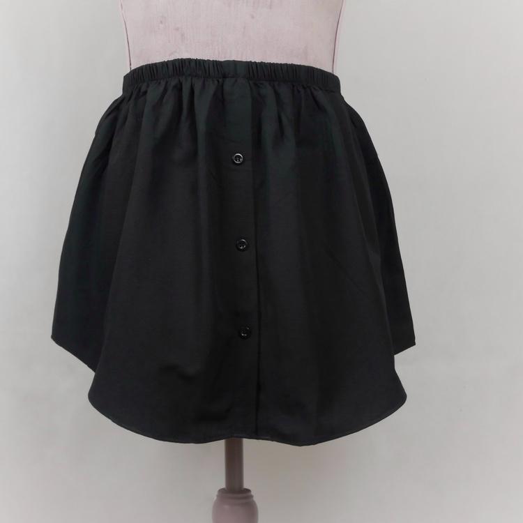 Löstagbar blusunderdel i färgen svart. Denna underkjol har tre knappar som går att knäppa upp