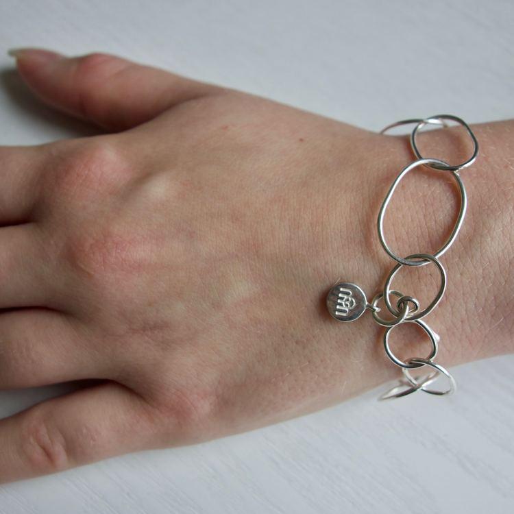 silverarmband gjort av öglor i olika storlekar. silver bracelet with round links