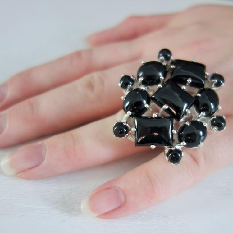 hand med stor silverring, ringen har infattade onyxstenar