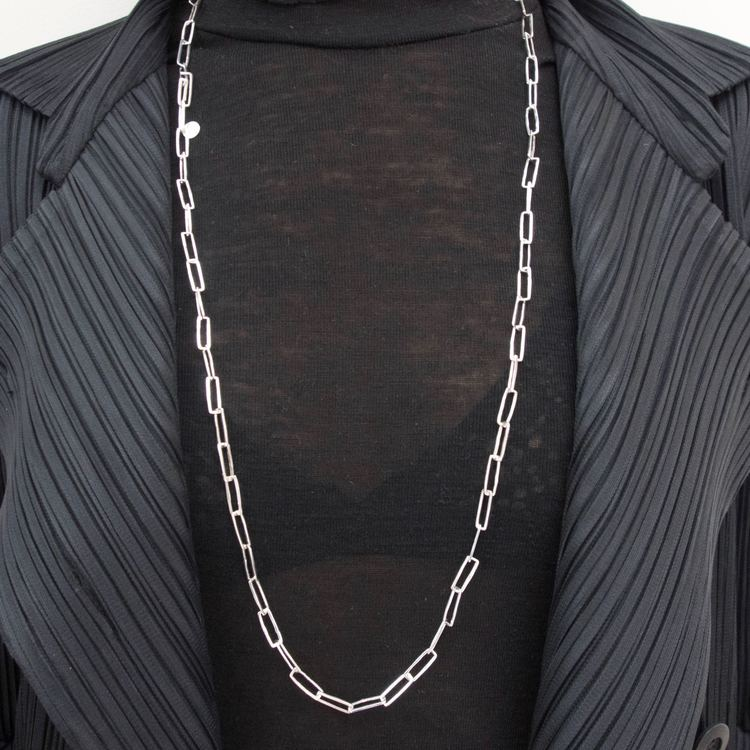 lång silverkedja med rektangulära länkar runt en hals med svarta kläder. long silver chain with rectangular links around the neck, black clothing.