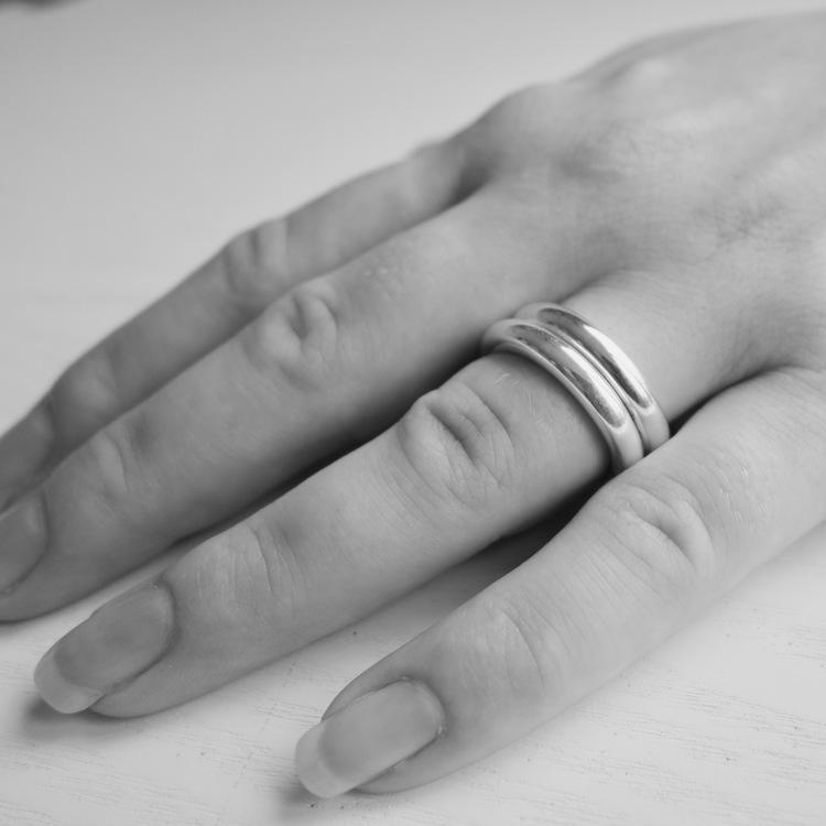 Närbild på hand där två enkla silverringar bärs på samma finger. hand with same two silver rings.