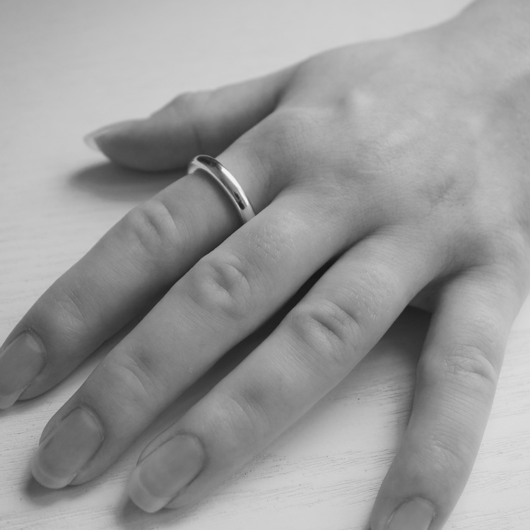 Närbild på hand där en enkel slät silverring. hand with a silver ring.