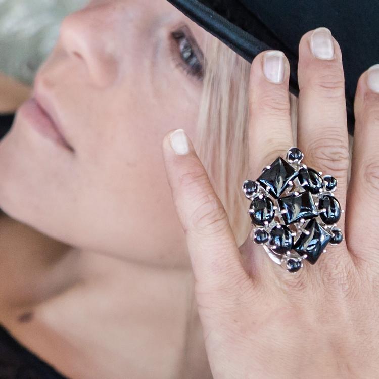 model med stor silverring som har infattade onyxstenar