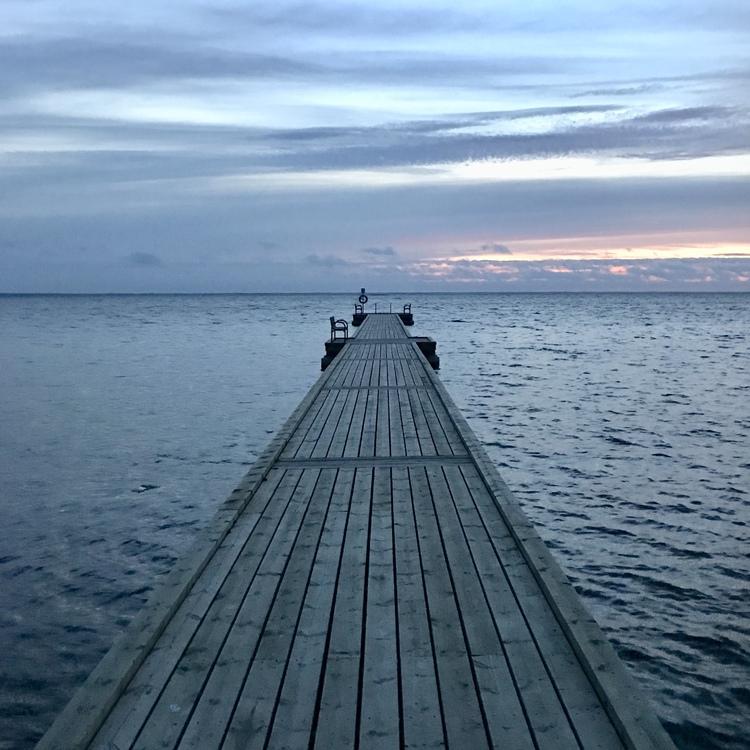en lång brygga i solnedgång. a long ponton in sunset.