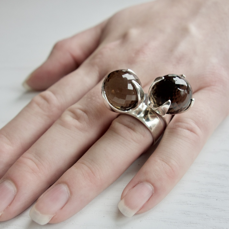 hand med två stora silverringar med rökkvarts. hand with two big silver rings with smokey quartz