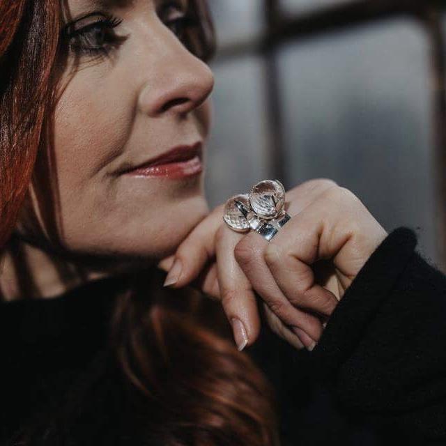 model med stora silverringar med facettslipade bergskristaller, två ringar på ett finger