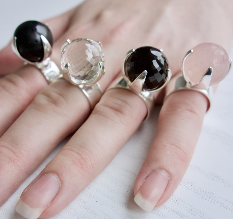 hand med stora silverringar med rosenkvarts, rökkvarts, onyx och kristallkvarts. hand with big silver rings with rose quartz, smokey quartz, onyx and crystal quartz