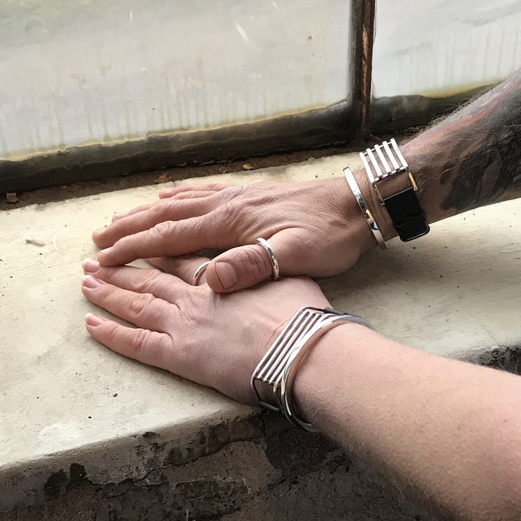 En manshand och en kvinnohand, bägge med samma unisexsmycken, släta silverringar och silverarmband med läder. man and women wearing the same jewelry, bracelets and silver rings, unisex.
