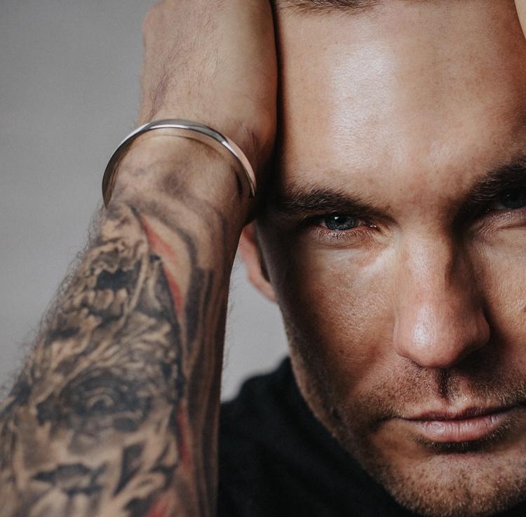 manlig modell med slätt enkelt armband. man wearing a massive silver bracelet