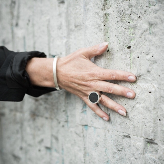 hand på vägg, stor silverring med onyx och silverarmband. hand on wall with bracelet and a big silver ring with onyx