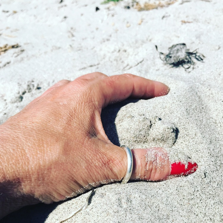 hand med slät silvering i sanden. hand with silver ring in the sand.