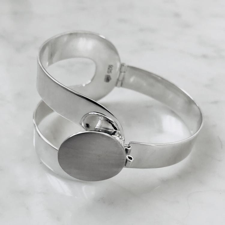 stort silverarmband, inspirerat av 70 talets pop- design, gångjärn och lås. Big silver bracelet with hinge and lock