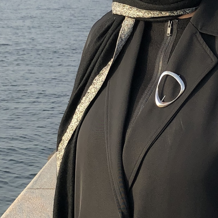 silverbrosch på en svart kavaj, silver brooch on a black jacket