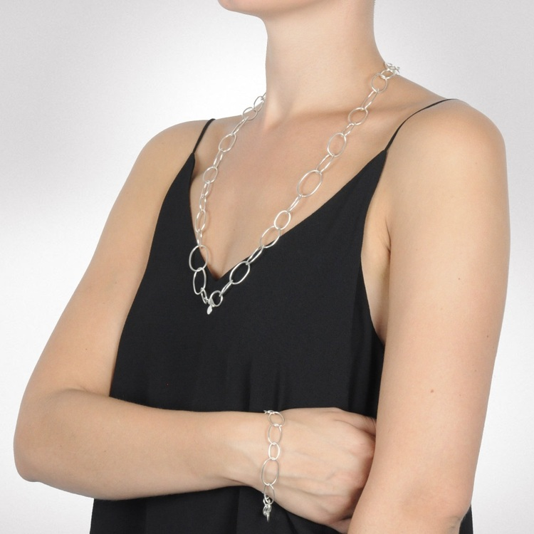 Kvinna med silverarmband och matchande långt silverhalsband. Woman with silver bracelet and matching long silver chain