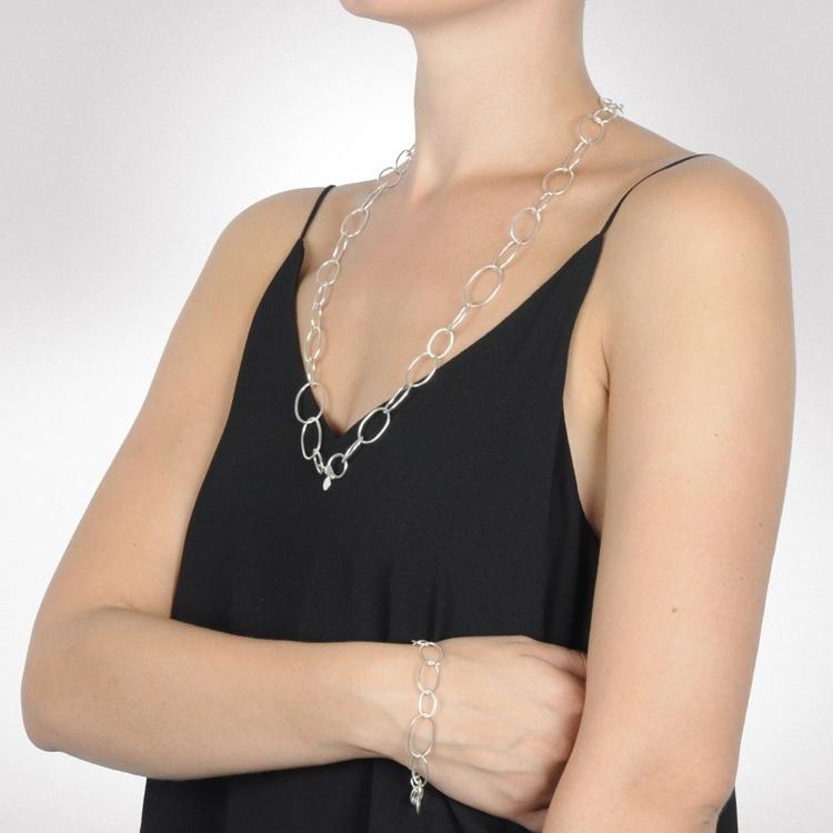 Kvinna med silverarmband och matchande långt silverhalsband. Woman with silver bracelet and matching long silver chain