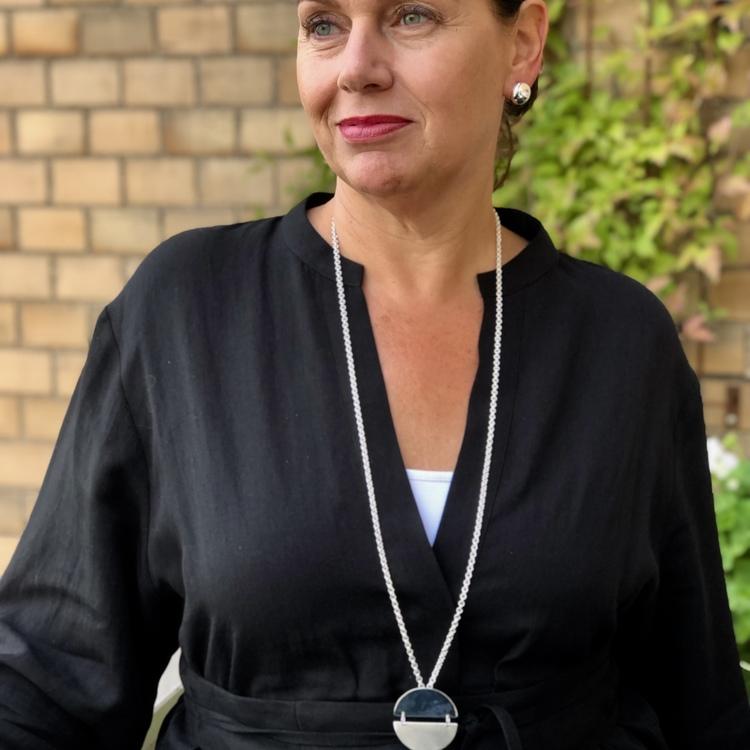 Kvinna med silverkedja och cirkelformat stort Silverhänge. Woman with silverchain and a big Silver pendant