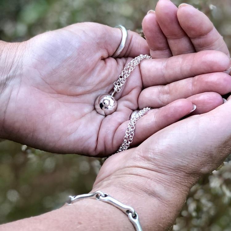 Litet silverhänge på silverkedja. Small silver pendant on a silver chain