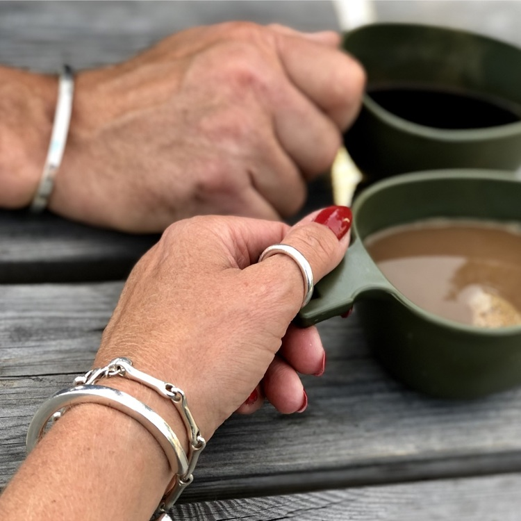 En manshand och en kvinnohand, bägge med samma unisexsmycken, silverring och armband. man and woman wearing the same jewellery, silver ring and bracelets.