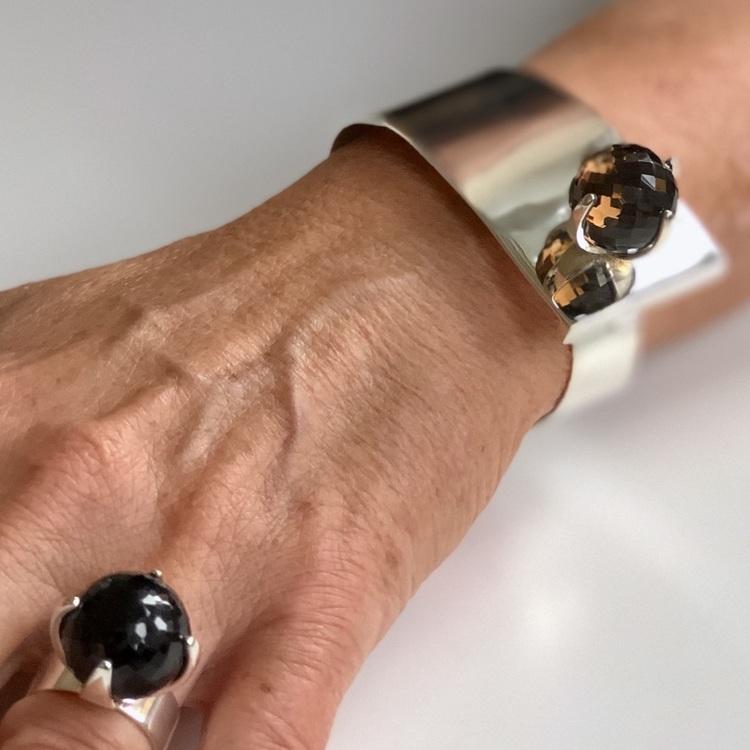 Hand med stor silverring och silverarmband med rökkvarts. Hand with big silverring and silver bracelet with smokey quartz.