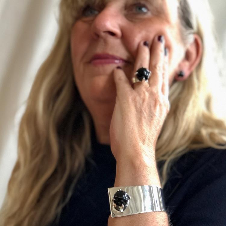 Kvinna med stor silverring och silverarmband med rökkvarts. Woman with big silverring and silver bracelet with smokey quartz.