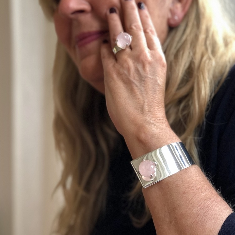 Kvinna med silverarmband  och stor ringa med rosenkvarts. Woman with silver bracelet and a big ring with rose quartz.