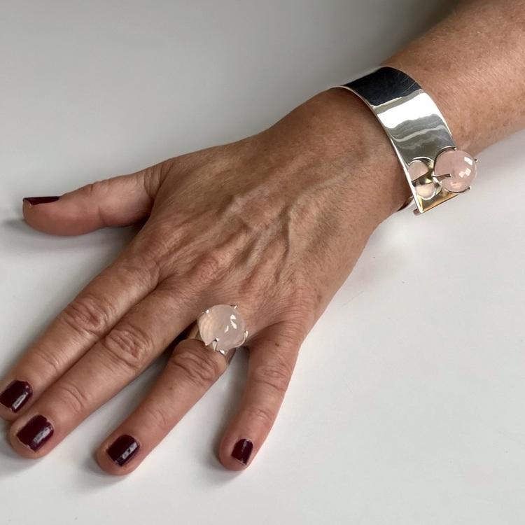 Hand med silverarmband  och stor ringa med rosenkvarts. Hand with silver bracelet and a big ring with rose quartz.