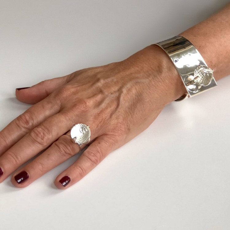 Arm med stort silverarmband och silverring med bergskristall. Hand with big silver bracelet and silverring with crystal quartz.