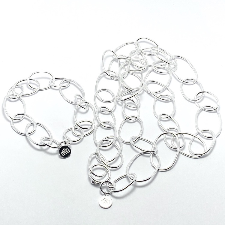 långt silverhalsband med runda länkar i olika storlekar med matchande armband. long silver chain with round links in various sizes with matchin bracelet.