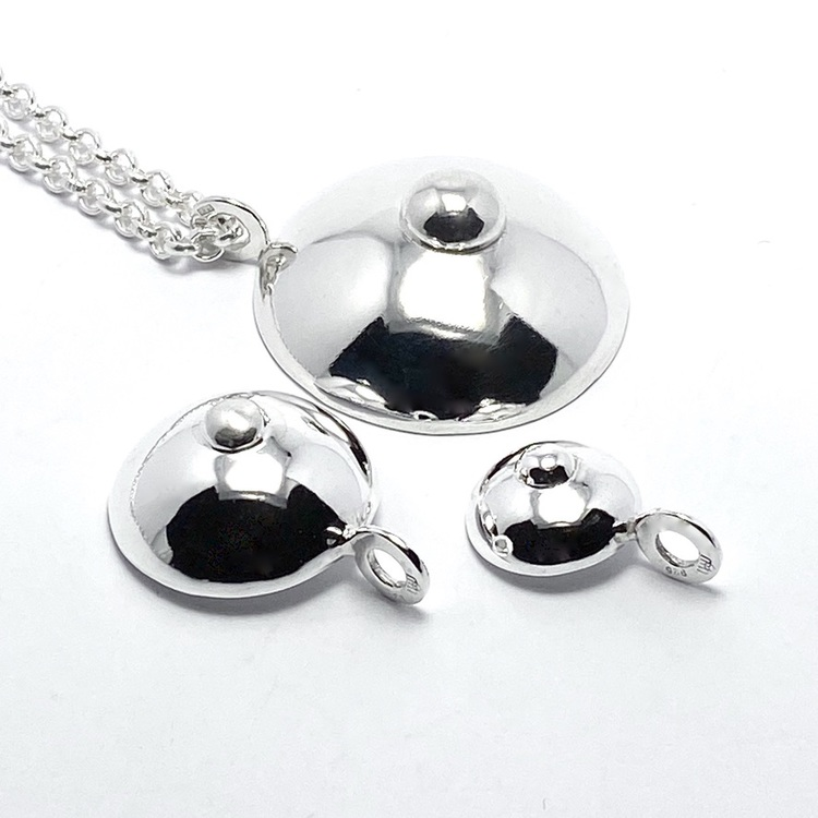 Silverhängen i form av hängbröst, i tre olika storlekar. Silver pendants in three sizes