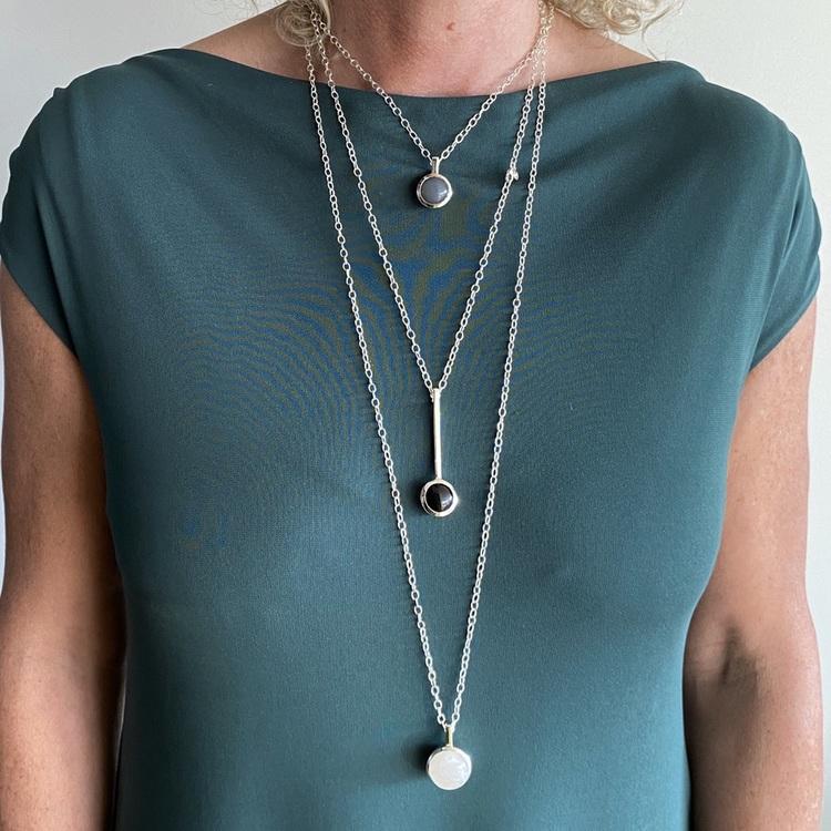 Modell med tre olika längder av silverkedjor och olika silverhängen. Model with three various lengths of silver chains with pendants