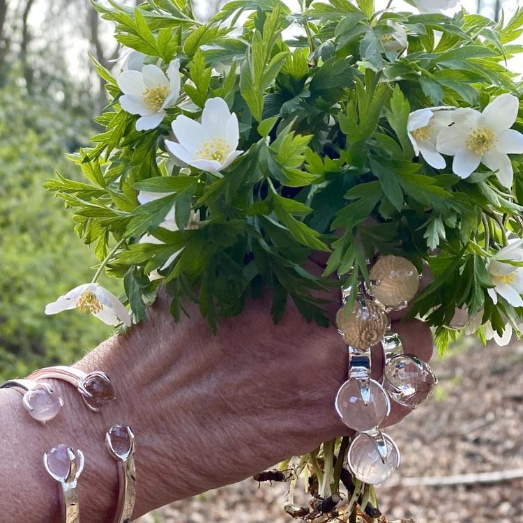 Hand med vitsippor och silverringar och armband, rosenkvarts och bergskristall.