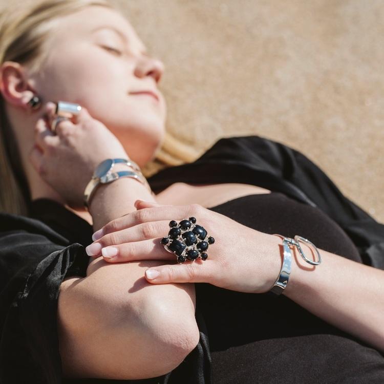 Kvinna med stora silversmycken och en stor silverring med svart onyx