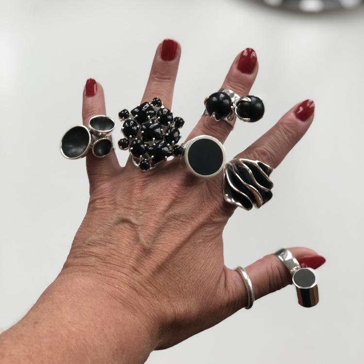 Hand med stora silverringar, oxiderade ringar eller med svart onyx