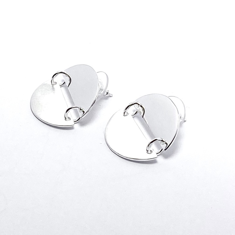Silverörhängen med två halvcirklar som bildar en cirkel. Silver earrings with two half circles.