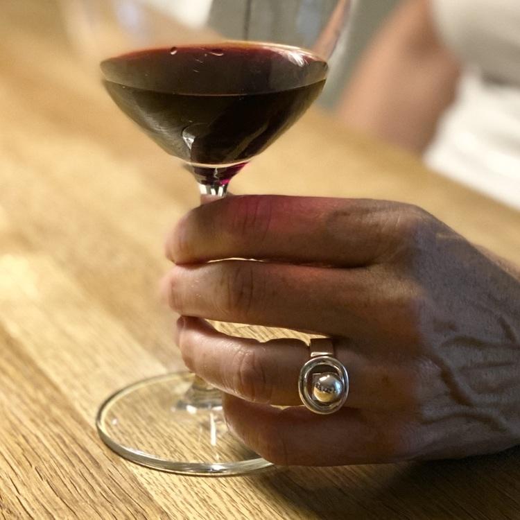 Hand med stor silverring och ett glas vin