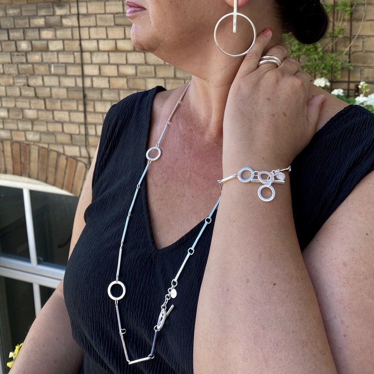 Silverarmband och silverhalsband med vackra silverstavar och cirklar. Silver bracelet and silver necklace with beautiful silver sticks and circles.