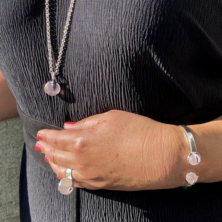 Kvinna med matchande armband, hänge, och ring med rosenkvarts. Woman with matching ring, pendant and bracelet with rose quartz