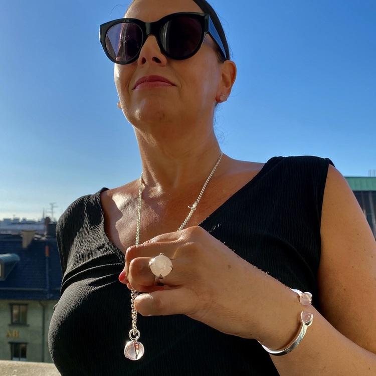 Kvinna med matchande armband, hänge, ring och örhängen med rosenkvarts. Woman with matching earrings, ring, pendant and bracelet with rose quartz