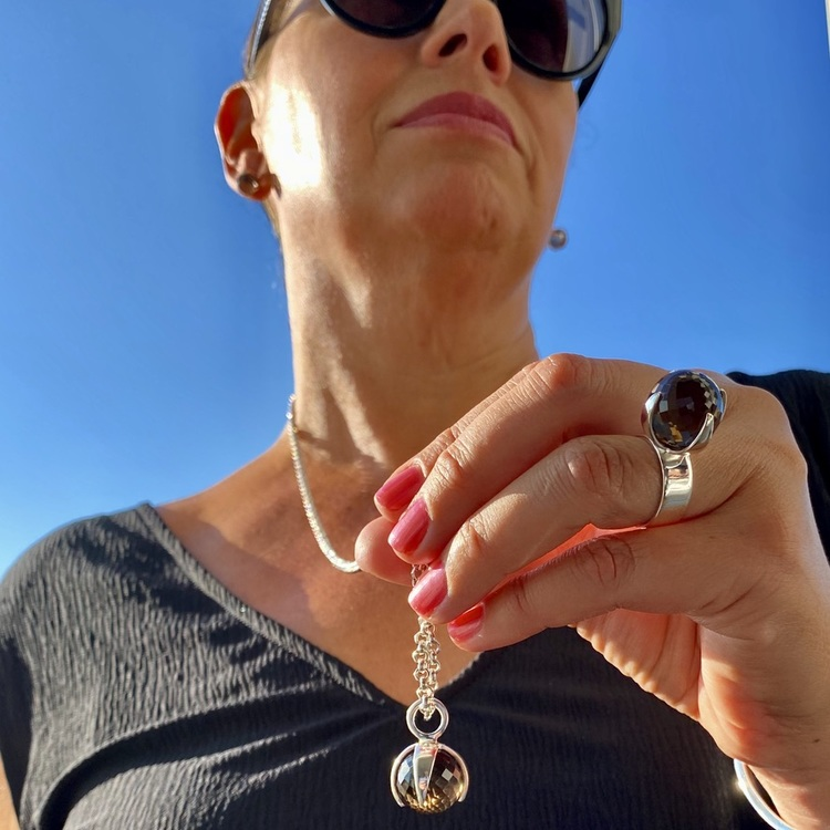 Kvinna med matchande armband, hänge, ring och örhängen med rökkvarts. Woman with matching earrings, ring, pendant and bracelet with smokey quartz