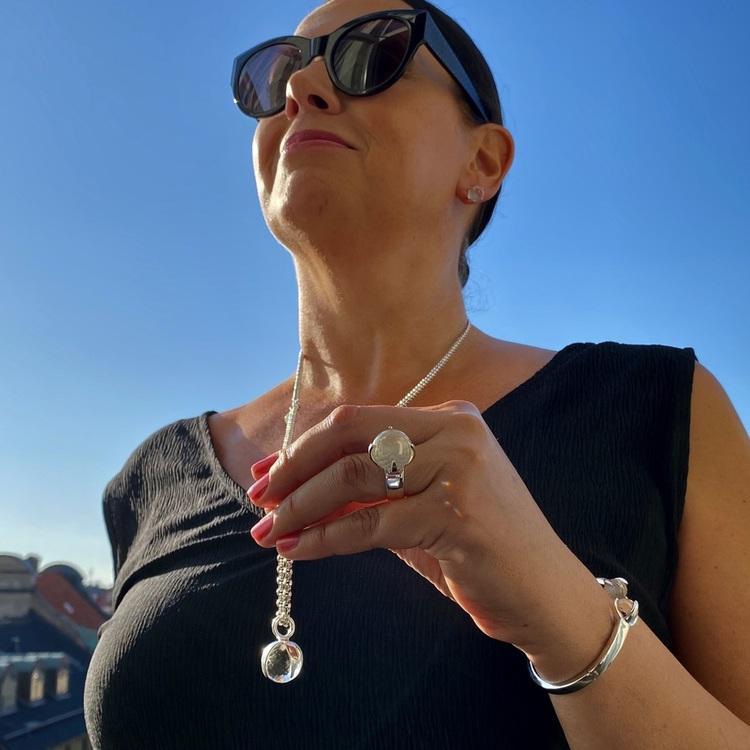 Kvinna med matchande armband, hänge, ring och örhängen med bergskristall. Woman with matching earrings, ring, pendant and bracelet with crystal quartz