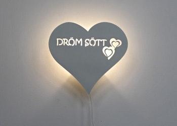 Vägglampa i form av ett hjärta med texten DRÖM SÖTT