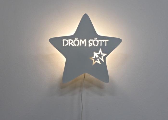 Stjärnformad vägglampa med texten DRÖM SÖTT