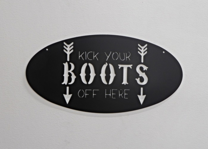 "Oval skylt med texten ""kick your BOOTS off here""."