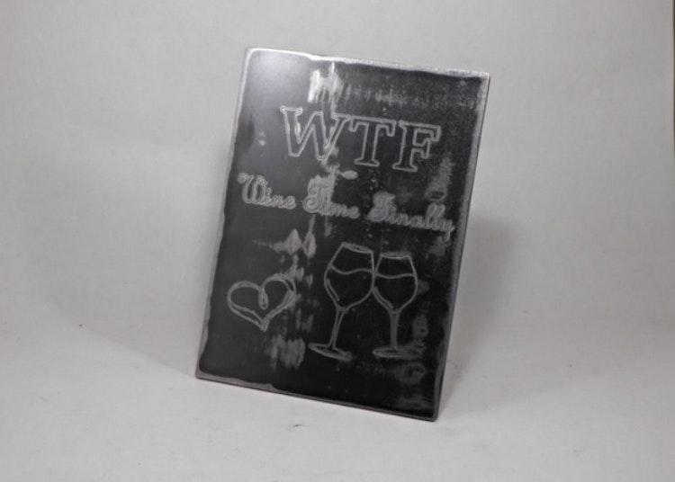 Graverad tavla i plåt med vinglas och texten WTF Wine Time Finally.