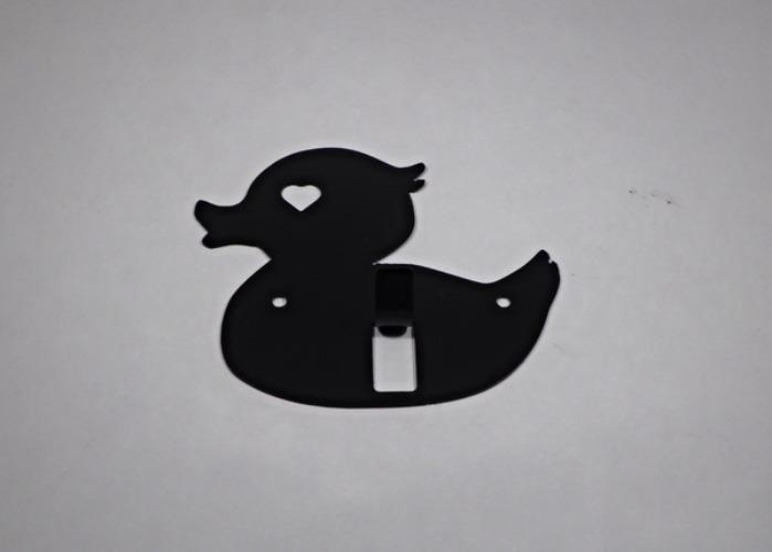 Hängare / Krok i plåt, figurskuren i formen av en badanka. Svart.